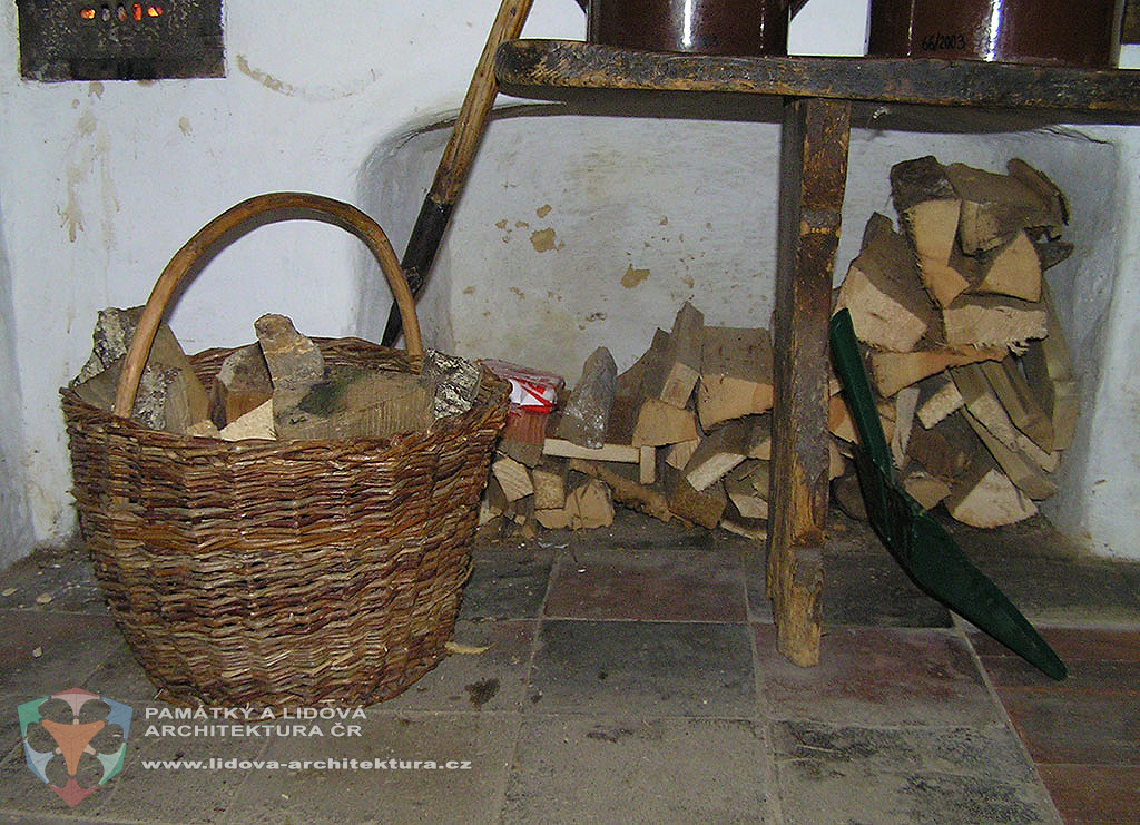 Palivové dřevo v proutěném koši a výklenku